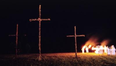 KKK members carry torches across a field in western Greene County Missouri in the early 1990's. (Copyright John S. Stewart/LEFTeyeSTORIES.com)
